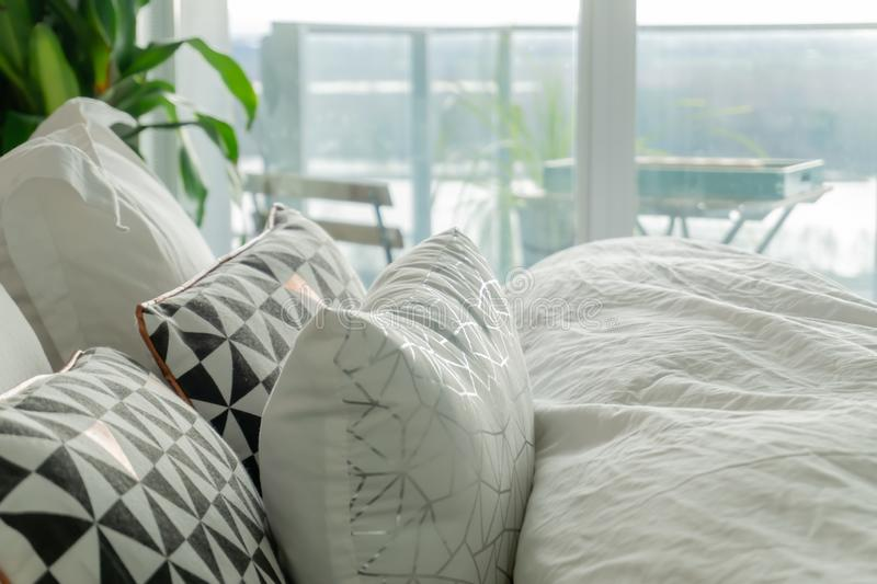 Fluffy, decorative pillows on a real bed, with wrinkled sheets and grey, black and white accent colors. Balcony view shows in the stock photography