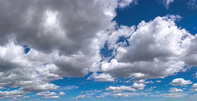 Fluffy gray and white cirrus clouds above horizon royalty free stock image