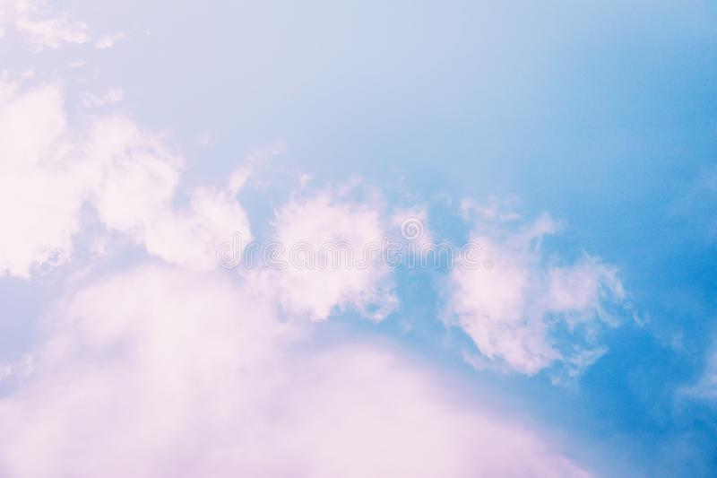 Fluffy light pink clouds on a blue sky background royalty free stock images