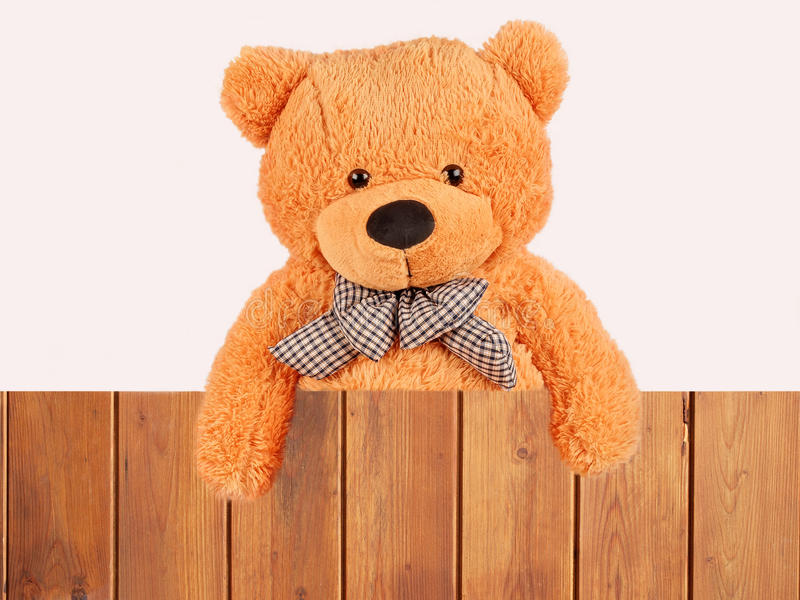 Fluffy plush teddy bear. Over wooden fence, studio shot royalty free stock images
