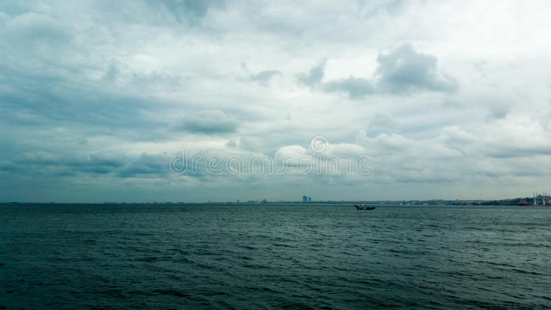 Fluffy rain clouds in the sky. And the sea royalty free stock photo