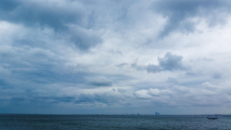 Fluffy rain clouds in the sky. And the sea royalty free stock photography