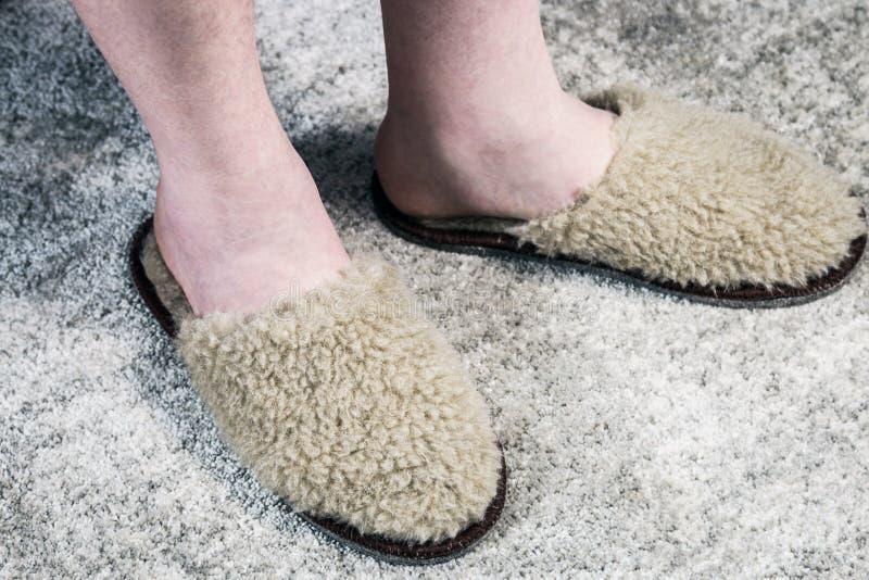 Fluffy Slippers on feet on the carpet stock image