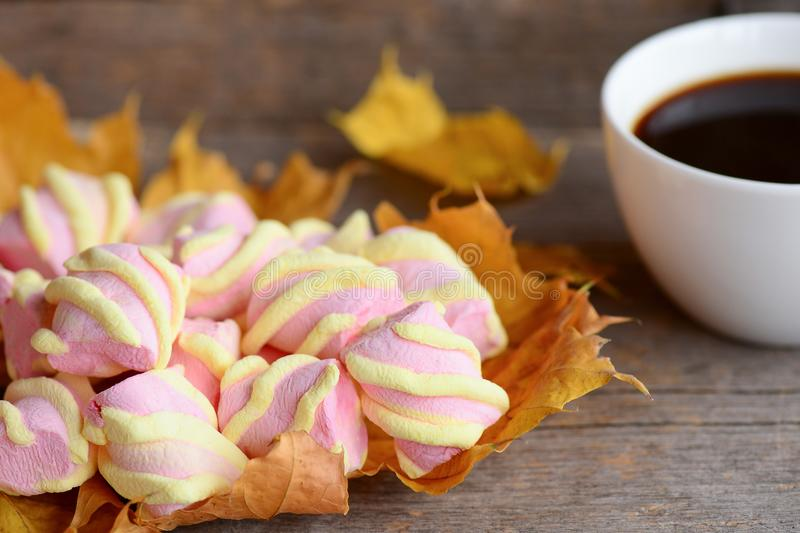 Fluffy sweet marshmallow candy on autumn yellow leaves, a cup of coffee on a wooden table. Autumn light breakfast or snack concept stock photos