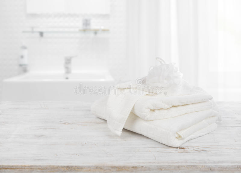 Fluffy towels and wisp of bast over blurred bathroom background stock photos
