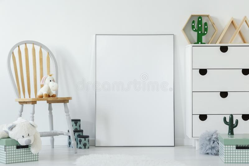 Fluffy toy placed on wooden chair in white baby room interior wi stock photos