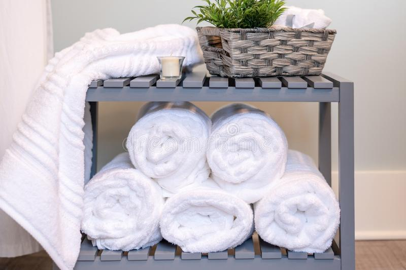 Fluffy white bath towels rolled and stacked stock photo