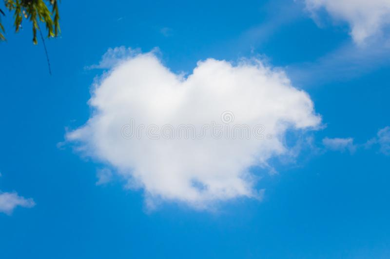 Fluffy white cloud in the form of a heart on the background of a blue sky_ royalty free stock photos