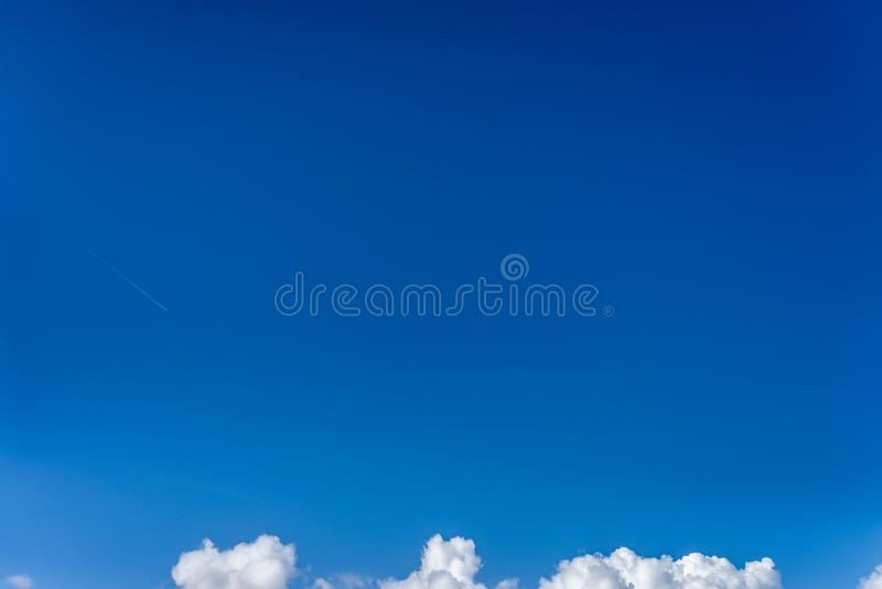 Fluffy white clouds against a bright, colorful blue sky stock photography