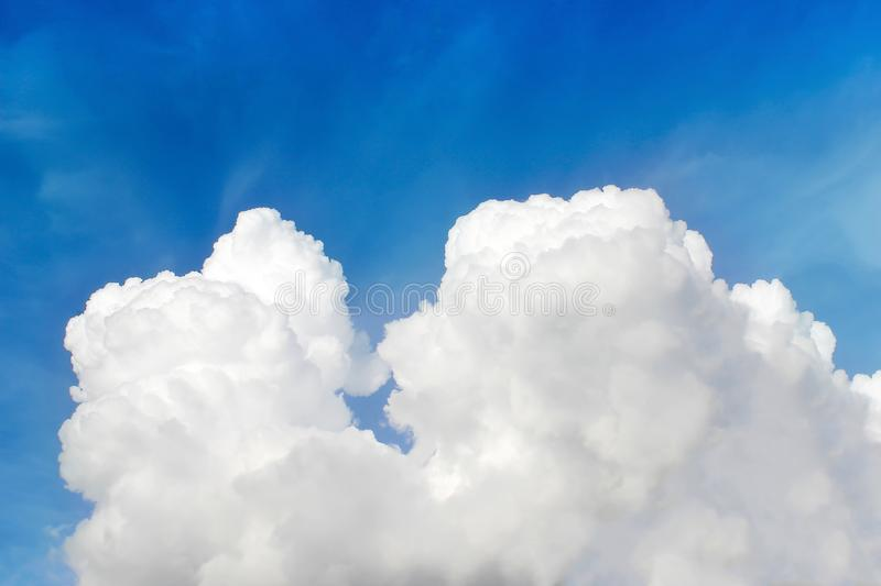Fluffy white clouds on bright blue sky background royalty free stock photography