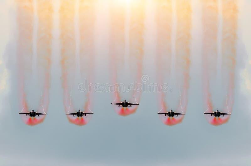 Fluga för fem jaktflygplan samman med röd rök arkivbild