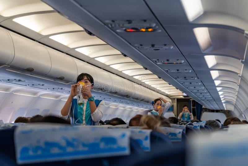 Flugbegleiter demonstrieren den richtigen Gebrauch von Sauerstoffmasken vorher lizenzfreie stockbilder
