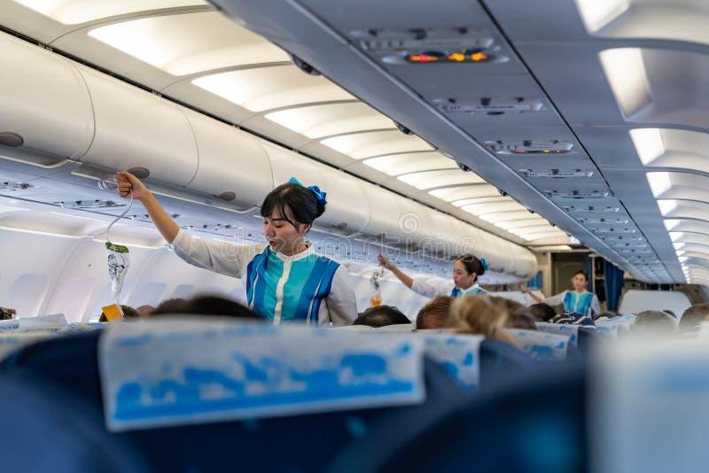 Flugbegleiter demonstrieren den richtigen Gebrauch von Sauerstoffmasken vorher stockfoto