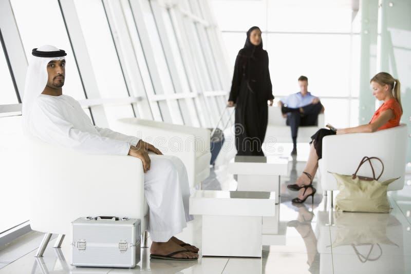 Fluggäste, die in Flughafenabflugaufenthaltsraum warten stockbild