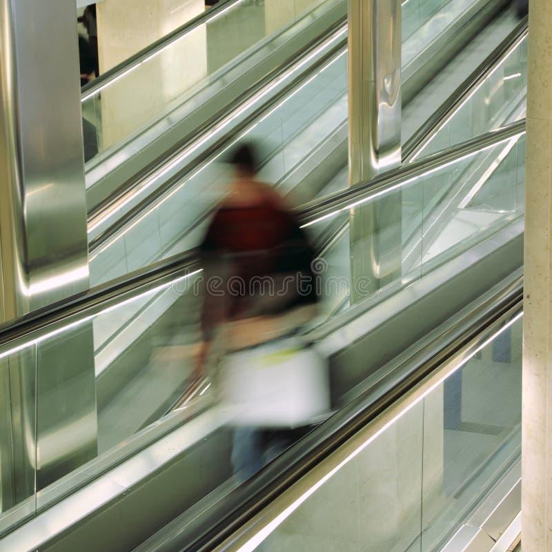 Fluggast auf escalatorat am Flughafen lizenzfreie stockfotos