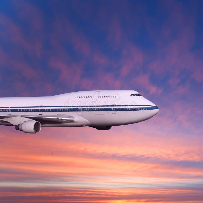 Fluggastflugzeug in den Wolken am Sonnenuntergang oder an der Dämmerung lizenzfreie stockfotografie