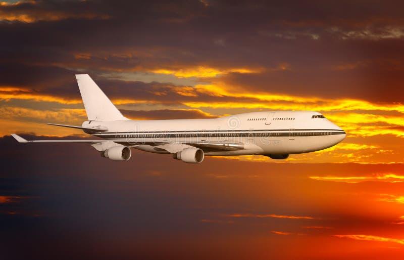 Fluggastflugzeug in den Wolken am Sonnenuntergang oder an der Dämmerung lizenzfreie stockfotos