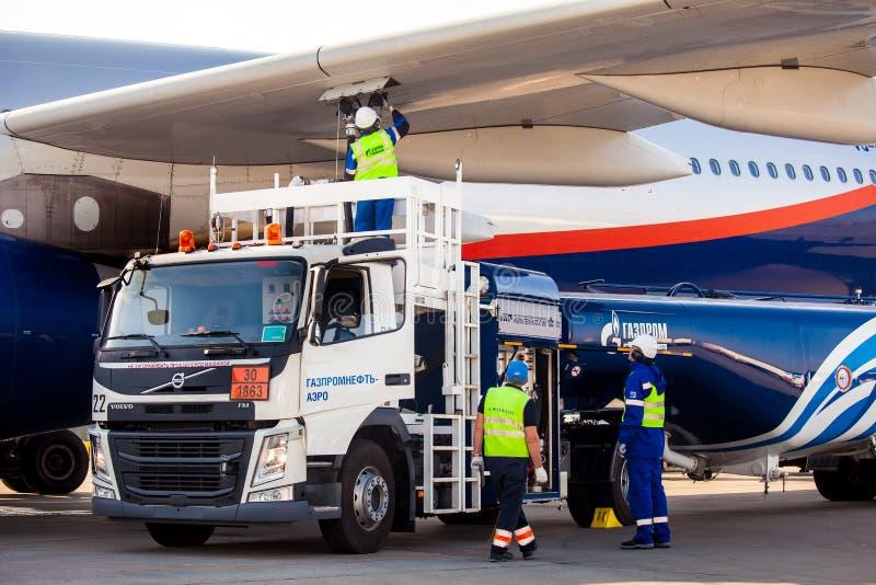 Flughafen-Gazprom-Firmenarbeitskräfte, welche die Flugzeuge wieder tanken lizenzfreie stockfotos