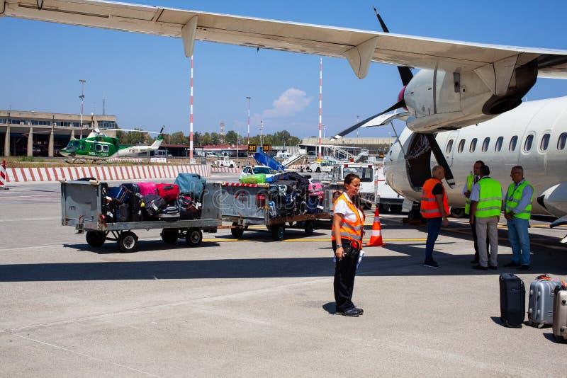 Flughafenarbeitskräfte, die nachdem das Flugzeug gelandet steuern stockbild