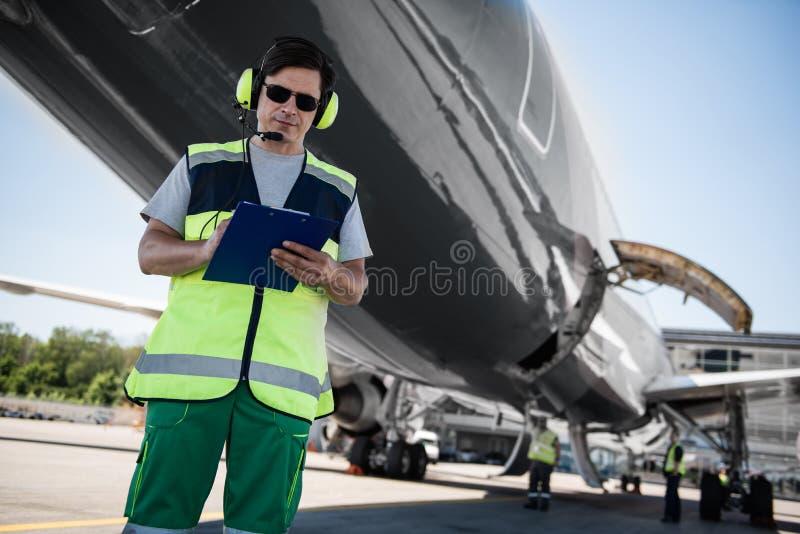 Flughafenarbeitskraft, die Dokumente während Grundmannschaftsmitglieder überprüfen Flugzeug vor dem Flug ergänzt lizenzfreie stockfotos