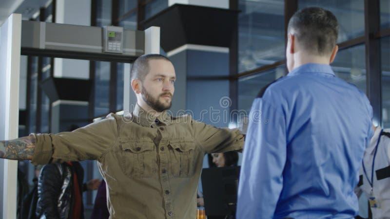 Flughafenarbeitskraft, die Passagier mit Metalldetektor überprüft stockbilder