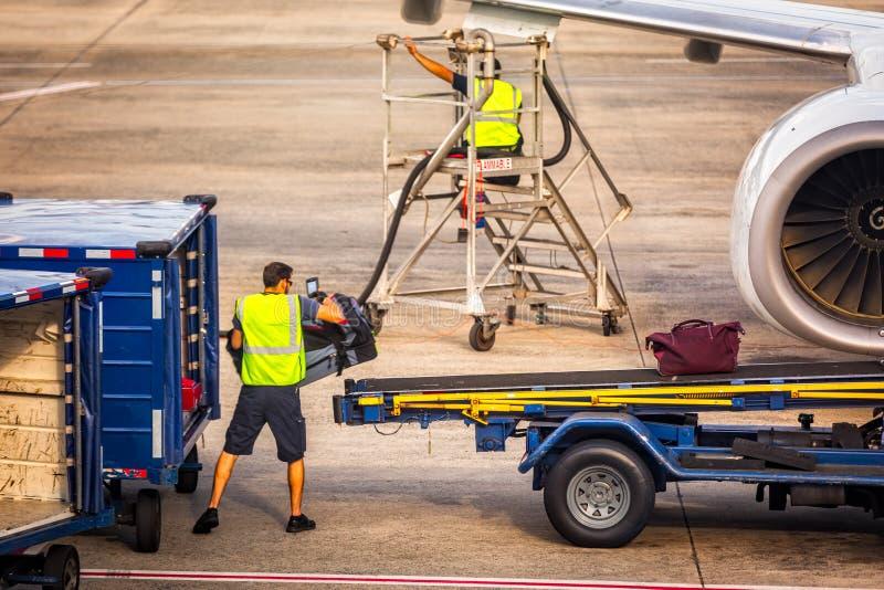 Flughafenarbeitskraft lädt Gepäck in ein Flugzeug stockfotos