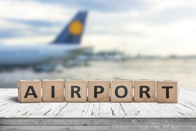 Flughafenwortschild auf einer hölzernen Oberfläche mit Flugzeug stockfoto