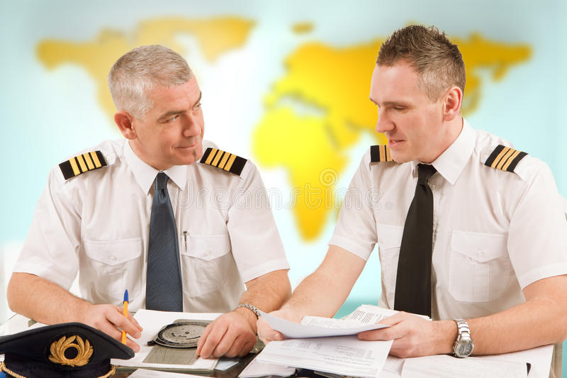 Fluglinienpiloten, die Papiere in ARO ausfüllen stockfotografie