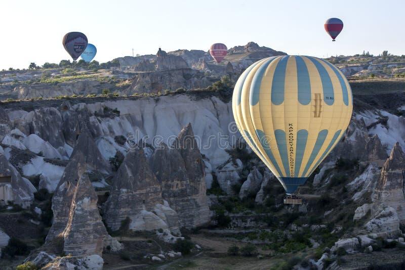 Flugor för en ballong för varm luft älskar ner dalen på soluppgång nära Goreme i den Cappadocia regionen av Turkiet royaltyfri bild
