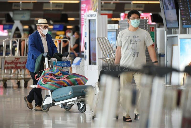 Flugreisende tragen Masken als Vorsichtsmaßnahme gegen den von Coronavirus verursachten Covid-19 lizenzfreie stockfotografie