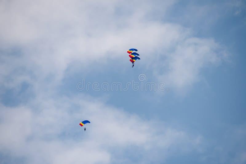 Flugschau Bukarests internationale NEIGUNG, Fallschirmsoldaten mit rumänischer Staatsflagge lizenzfreie stockbilder