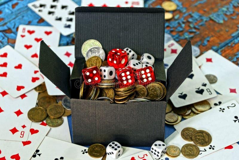 Flugschreiber voll Münzen und Spielwürfel ist auf den Karten auf dem Tisch lizenzfreies stockbild