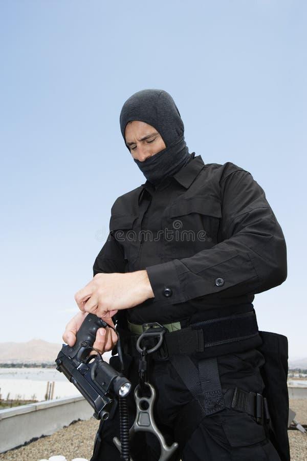 FLUGSMÄLLA Team Officer Loading Pistol arkivbilder