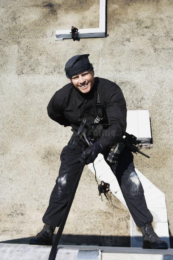 FLUGSMÄLLA Team Officer Rappelling från byggnad arkivfoto