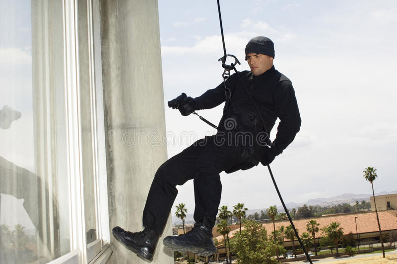 FLUGSMÄLLATeam Officer Rappelling And Aiming vapen royaltyfria bilder