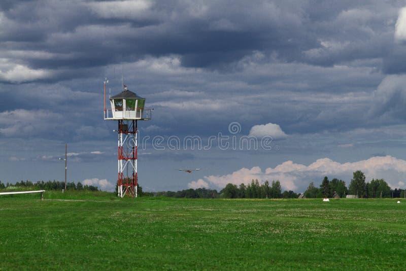 Flugsteuerungsturm auf einem kleinen Grasflugplatz mit Segelflugzeuglandung im Hintergrund in einem schlechten Wetter stockbild