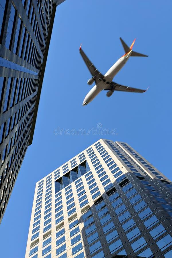 Flugzeug über Bürohaus stockbilder