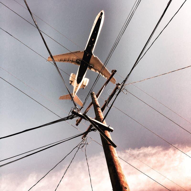 Flugzeug über Stromleitungen stockfotografie