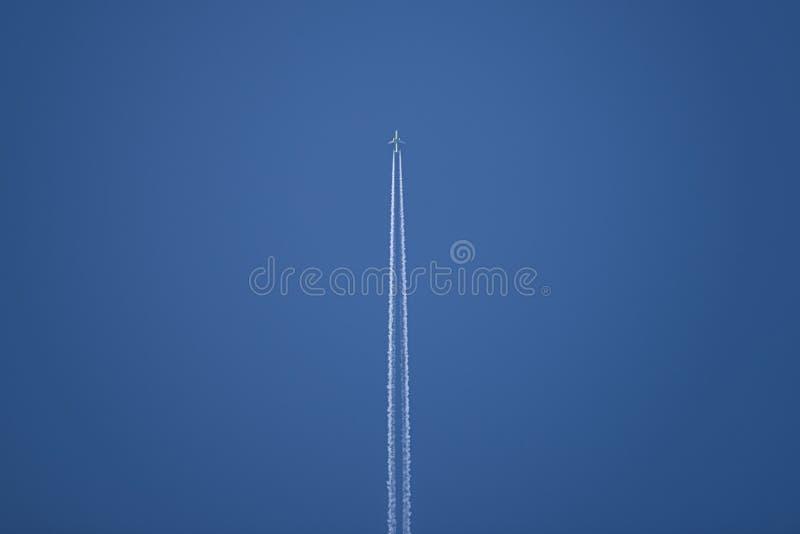 Flugzeug Contrail gegen blauen Himmel Die Ansicht von der Unterseite lizenzfreie stockbilder