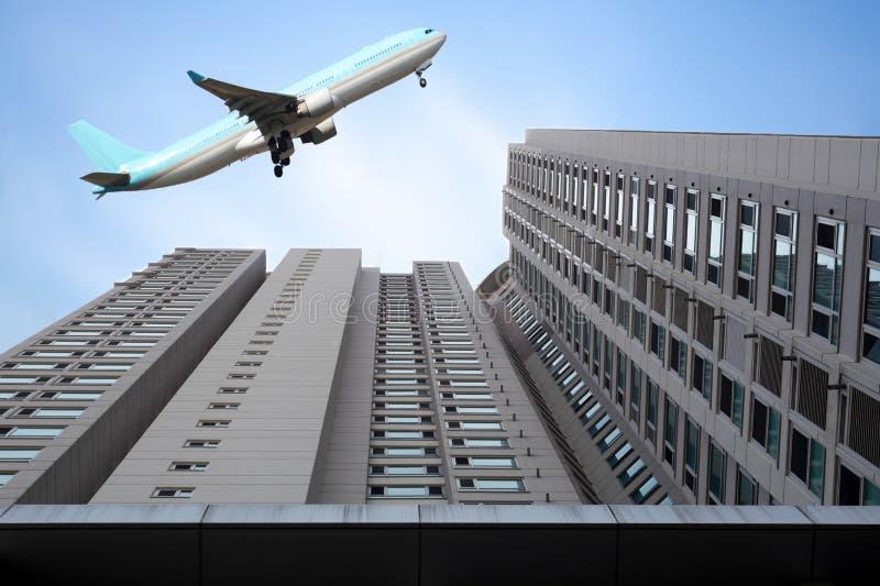 Flugzeug, das über Hochhäuserhimmelschaber fliegt stockfoto