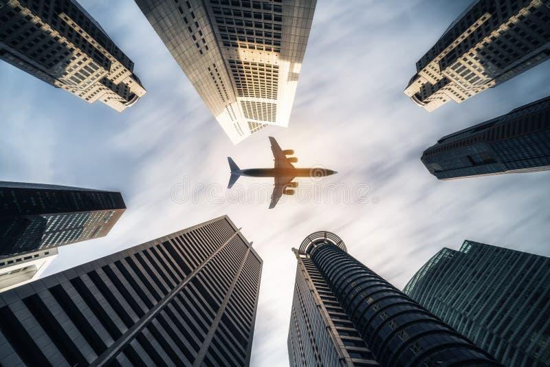 Flugzeug, das über Stadtgeschäftsgebäude, Hochhaus skyscrap fliegt stockfotografie