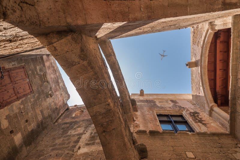 Flugzeug, das durch über altes Maurerarbeitgebäude in der alten Stadt von Rhodos überschreitet Griechische Insel von Rhodos stockbild