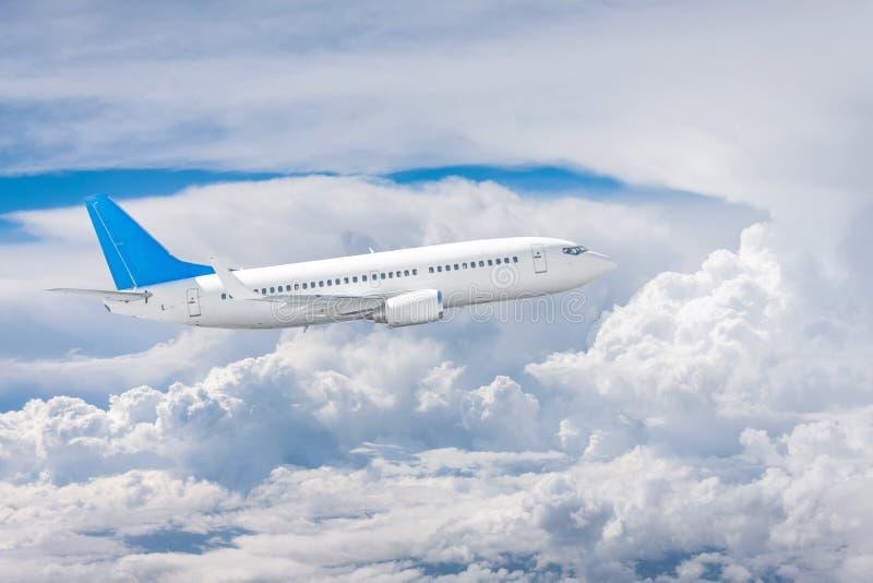Flugzeug fliegt unter den starken Sommerwolken stockbild