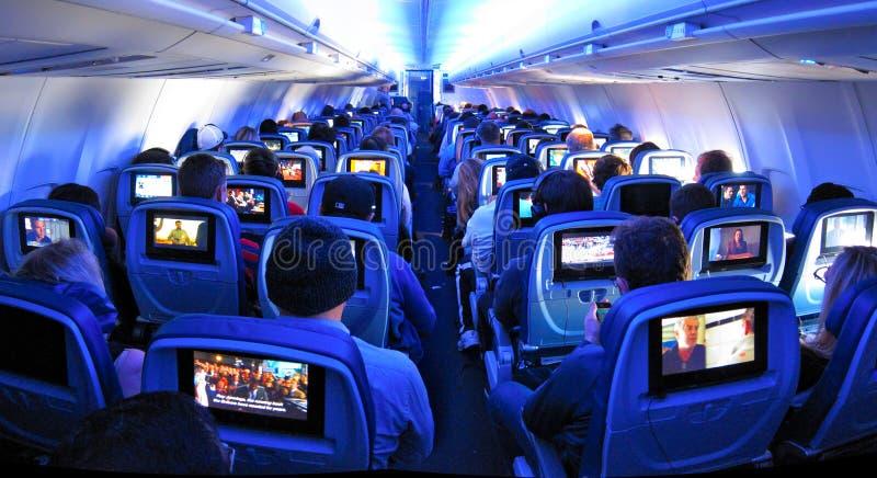 Flugzeug-Passagiere, Sitze und Fernsehschirme stockbilder