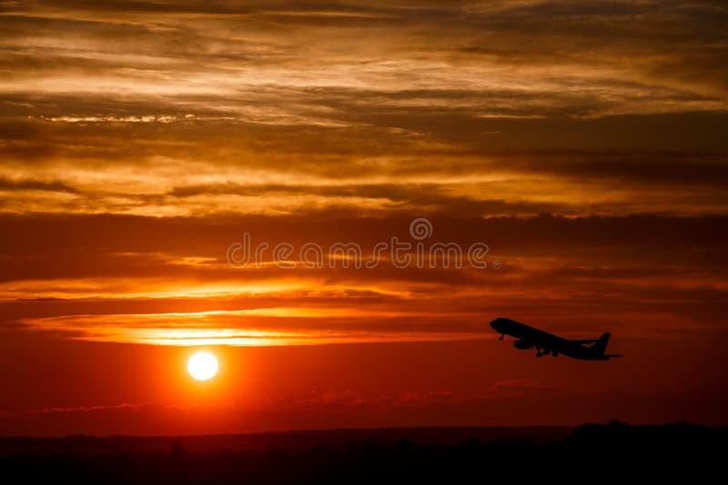 Flugzeug am Sonnenunterganghimmel in der Luft mit Raum für Text Silhouett lizenzfreie stockfotos