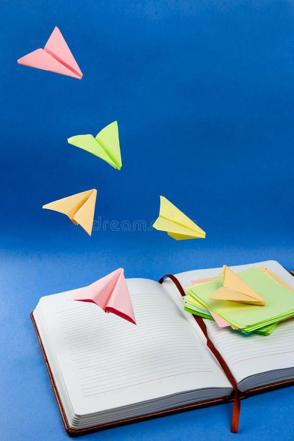 Flugzeuge hergestellt von den bunten Briefpapieren, die über das Notizbuch fliegen lizenzfreies stockbild