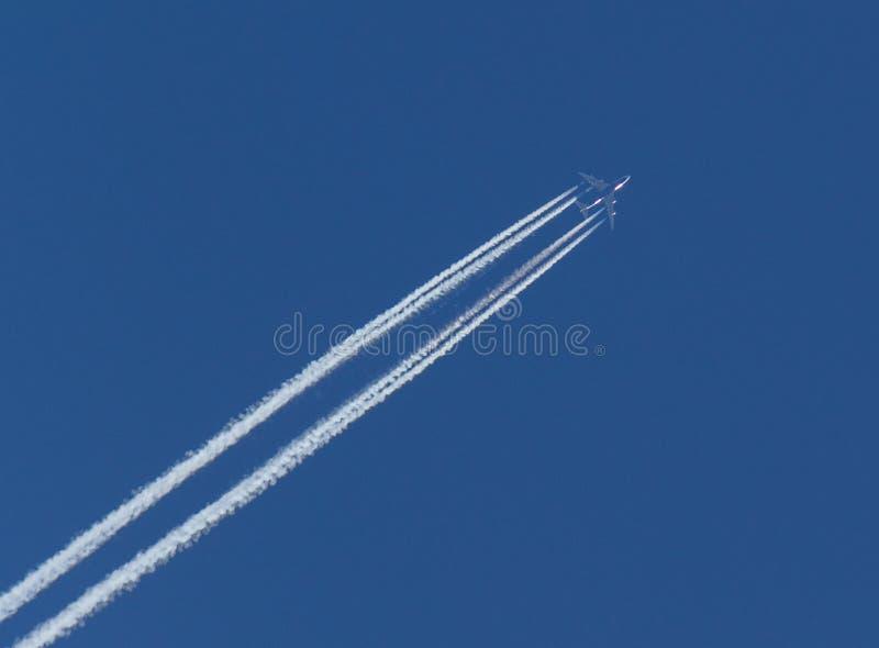 Flugzeuge und diagonale Kondensstreifen oder Contrails auf blauem Himmel stockfotos