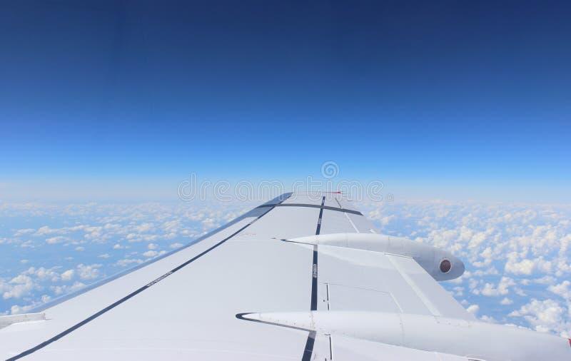 Flugzeugflügel im Himmel lizenzfreie stockbilder