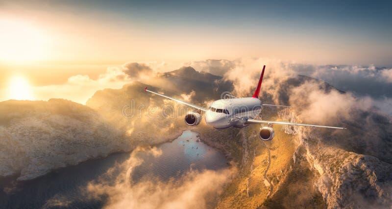 Flugzeugfliegen über Bergen und tiefen Wolken bei Sonnenuntergang lizenzfreies stockfoto