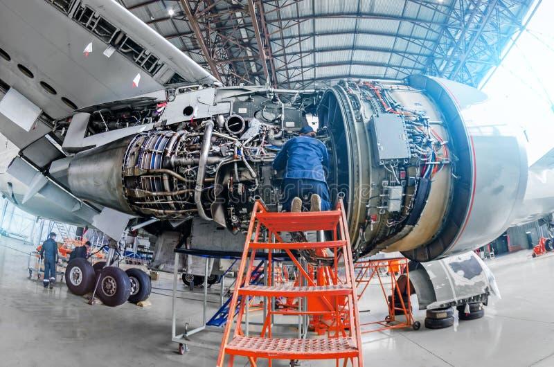 Flugzeugmechaniker bestimmen Reparaturstrahltriebwerk durch offene Luke lizenzfreie stockfotografie